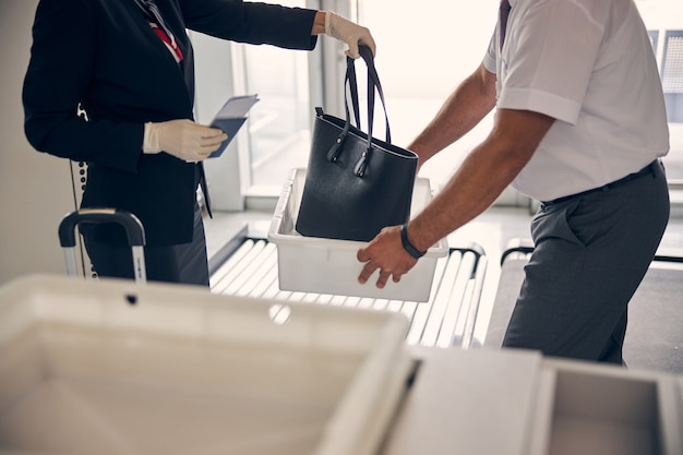 Close-up van vrouwelijke reiziger die elegante handtas in witte doos stopt terwijl luchthavenmedewerker container voor bagage vasthoudt