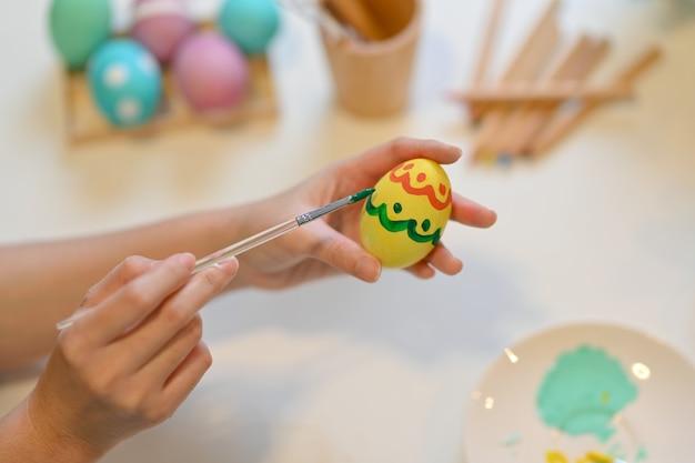 Close-up van vrouwelijke schilderij easter egg, pasen festival thuis voorbereiden