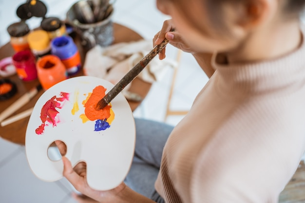 Close up van vrouwelijke schilders hand met een kwast