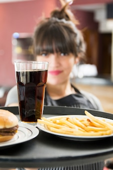 Close-up van vrouwelijke serveerster serveren drankjes met hamburger en frietjes