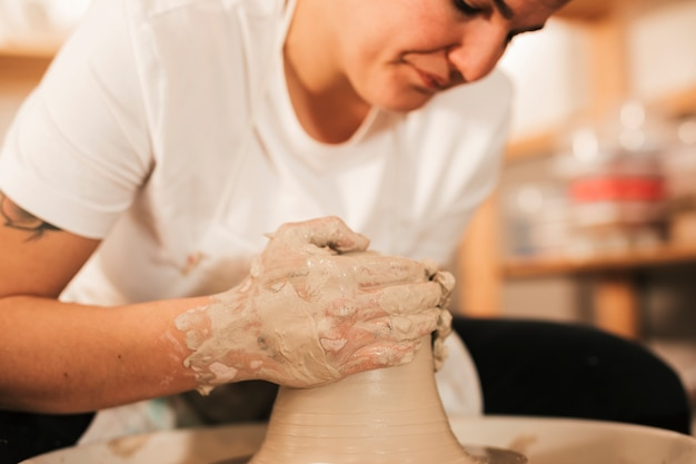 Close-up van vrouwelijke vakman die detail geven aan de klei op aardewerkwiel