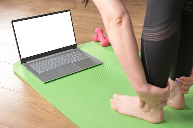 Close-up van vrouwelijke voeten en handpalmen op yogamat met laptop. mensen die yoga online beoefenen. concept van video-trainingsklasse op digitale apparaten.