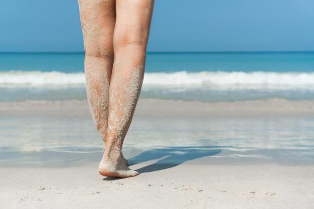 Close up van vrouwelijke voeten wandelen in zandstrand naar water