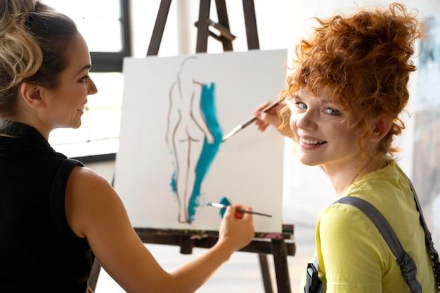 Close-up van vrouwen die samen op canvas schilderen