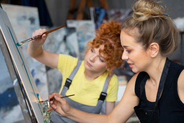 Close-up van vrouwen die schilderen met penselen