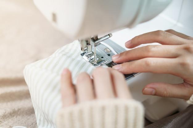 Close-up van vrouwenhand die de naaimachine met behulp van