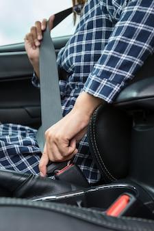 Close-up van vrouwenhand die een veiligheidsgordel in de auto vastmaken
