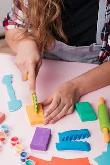 Close-up van vrouwenhand die kleurrijke klei op lijst snijdt