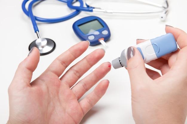 Close-up van vrouwenhanden die hoge bloedsuikerspiegel met glucometer testen