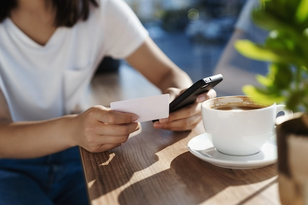 Close-up van vrouwenhanden die op koffietafel leunen, die mobiele telefoon en plastic creditcard houden.