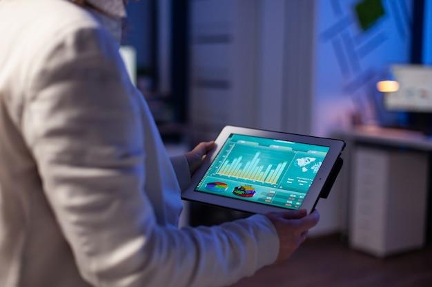 Close-up van vrouwenhanden die op tablet typen en financiële grafieken controleren die 's avonds laat in het startbureau staan. manager die sociaal netwerk gebruikt, sms't en blogt overuren maken voor werk