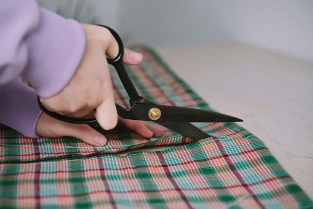 Close-up van vrouwenhanden die schaar houden en geruite stof voor het naaien van kleren snijden