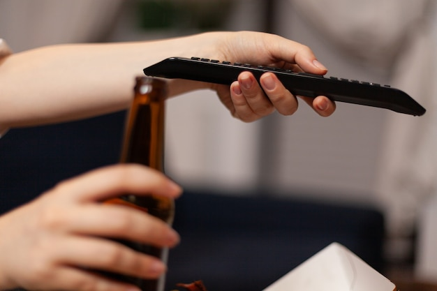 Close-up van vrouwenhanden die van kanaal veranderen met behulp van afstandsbediening kijken naar entertainmentkomediefilm