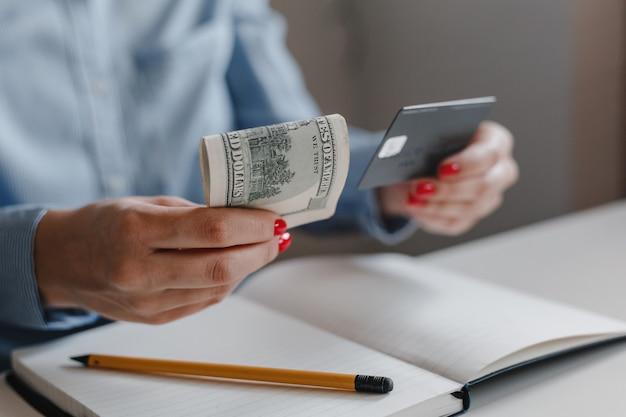 Close-up van vrouwenhanden met rode spijkers die de bankbiljetten van honderd dollarsgeld en een zwarte creditcard houden