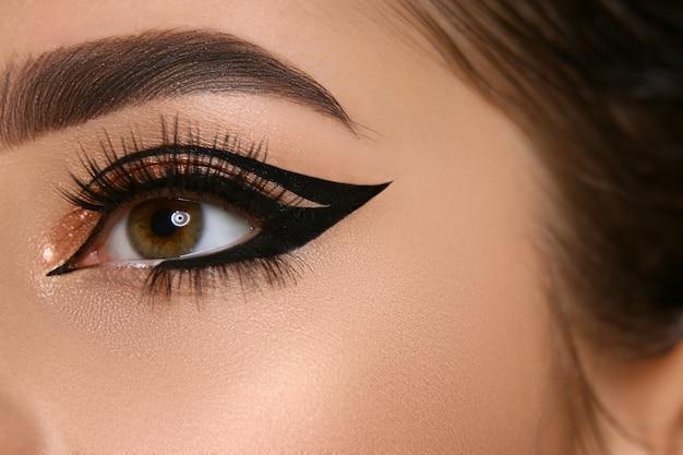Close-up van vrouwenoog met sexy eyeliner en gouden schaduw