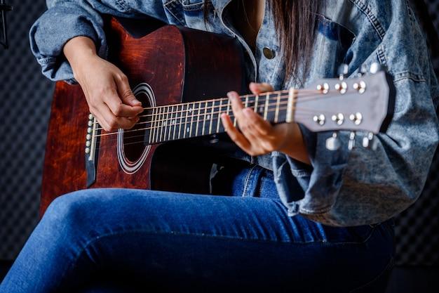 Close-up van vrouwenvingers die bemiddelaar vasthouden met een gitaar die een lied opneemt in de opnamestudio