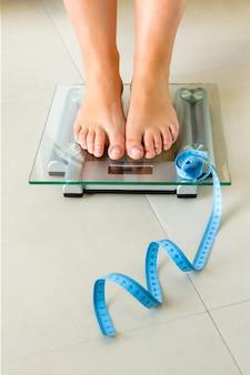 Close-up van vrouwenvoeten die zich op badkamersschaal en een meetlint bevinden. gezondheid en gewicht concept.