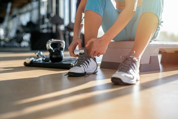 Close up van vrouwtjes handen schoenveters koppelverkoop voor training in de sportschool.