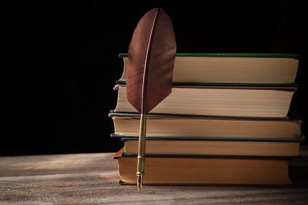 Close-up van vulpen dichtbij stapel oude boeken op zwarte
