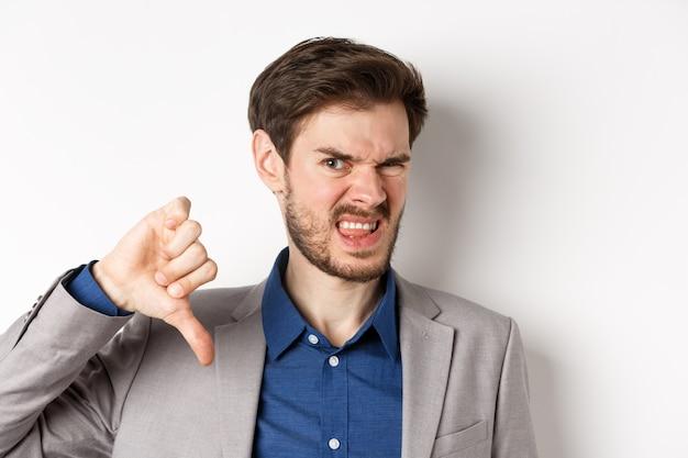 Close-up van walgen man in pak boos grimassen, duimen naar beneden tonen, negatieve emotie, witte achtergrond uitdrukken. Premium Foto