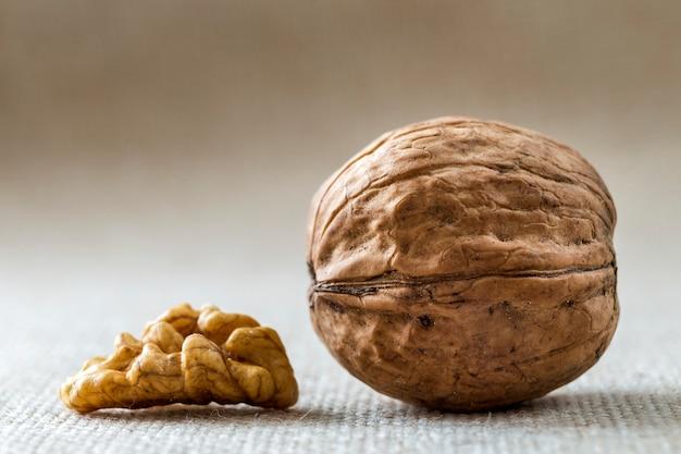 Close-up van walnoot in houten shell en pitten geïsoleerd op lichte kopie ruimte achtergrond. gezonde natuurvoeding concept.