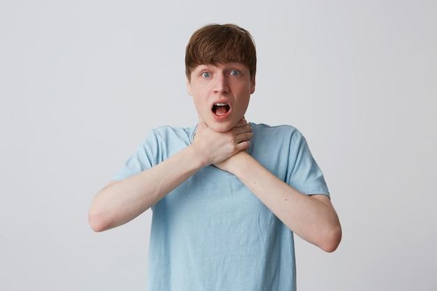 Close-up van wanhopige jonge man met beugels op tanden draagt blauwe t-shirt hebben problemen