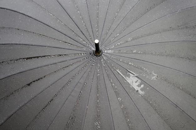 Close-up van waterdruppels die op de zwarte paraplu staan na de regen, een kleine scherptediepte