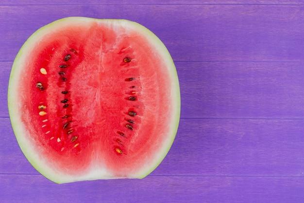 Close-up van watermeloen half op paarse achtergrond met kopie ruimte