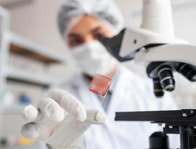 Close-up van wazige wetenschapper glazen glijbaan houden
