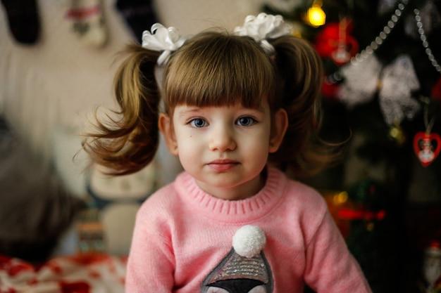 Close-up van weinig kaukasisch meisje in roze sweater met een nieuwe jaarboom thuis