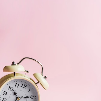 Close-up van wekker tegen roze achtergrond