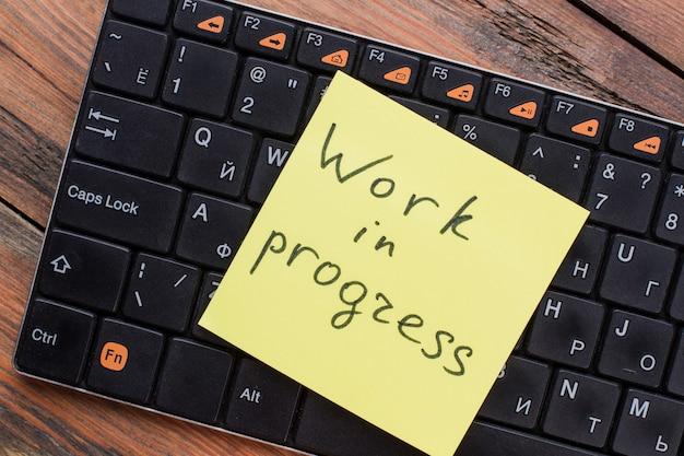 Close-up van werk in uitvoering notitiebericht op toetsenbord. geel notitiepapier.