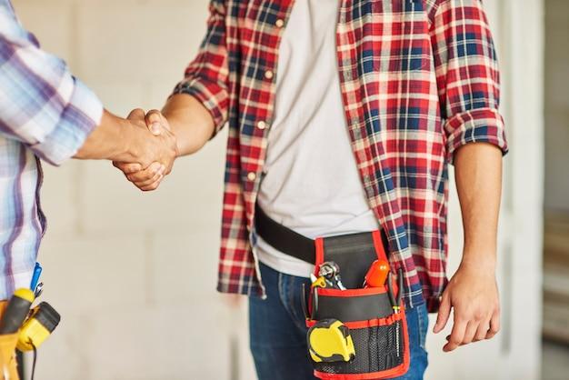 Close-up van werknemers die samenwerken en handen schudden