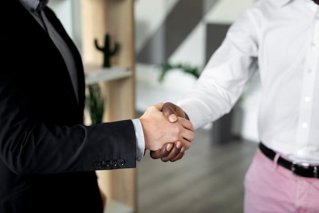 Close up van werknemers handen schudden