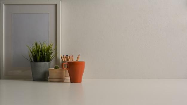 Close-up van werkruimte met mock up frame plant pot briefpapier en kopieer de ruimte in kantoor aan huis