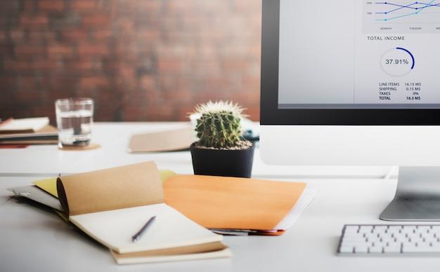 Close-up van werkruimtebureau met computer en blocnote