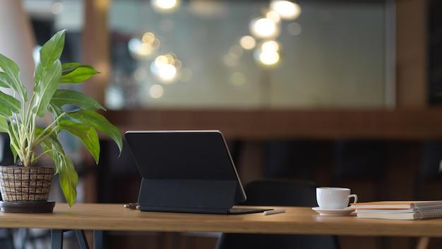 Close-up van werktafel met digitale tablet, koffiekopje, notebooks en plant pot in kantoorruimte