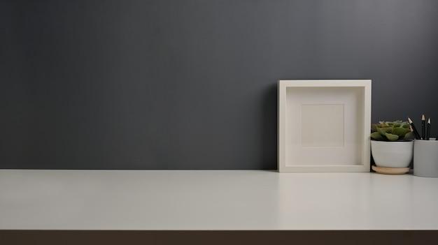 Close-up van werktafel met kopie ruimte, mock-up frame en plantenpotten in kantoor aan huis kamer