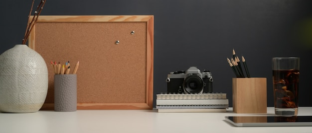 Close-up van werktafel met mock up prikbord, briefpapier, camera, leveringen en kopie ruimte in kantoor aan huis kamer