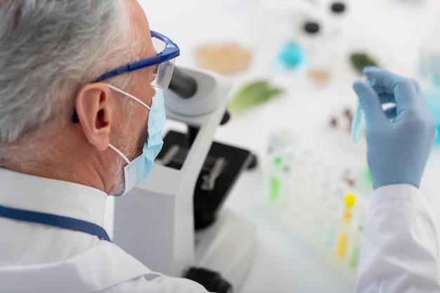 Close-up van wetenschapper die met microscoop werkt