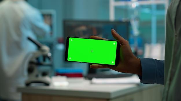 Close up van wetenschapper vrouw met horizontale telefoon met groene mockup in modern uitgerust lab. team van microbiologen die vaccinonderzoek doen en schrijven op apparaat met chroma key, geïsoleerd display.
