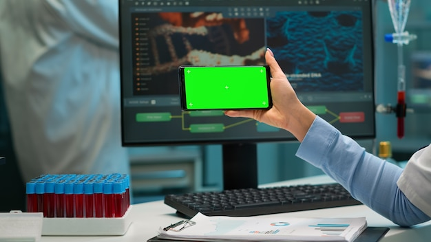 Close up van wetenschapper vrouw met smartphone met groene mockup in modern uitgerust lab. team van microbiologen die vaccinonderzoek doen en schrijven op apparaat met chroma key, geïsoleerd display.