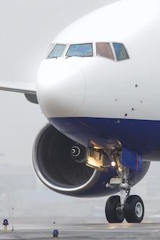 Close-up van wide-body vliegtuig dat op de landingsbaan na de landing belast, weinig bewolking, slecht zicht, mistig weer in het koude seizoen