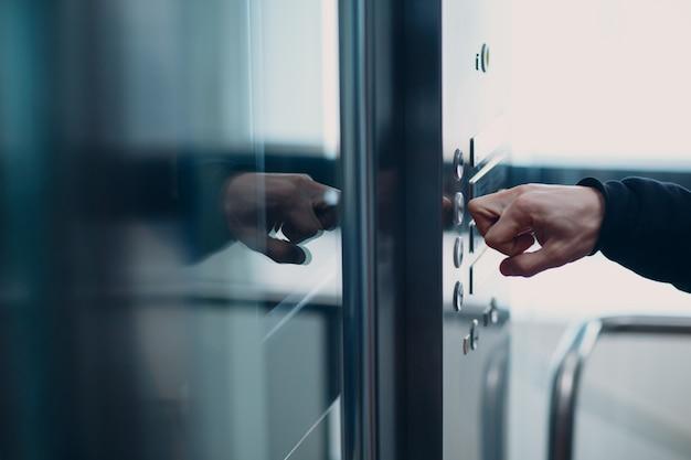 Close-up van wijsvinger knokkel op de knop lift tijdens coronavirus pandemie covid-19 quarantaineconcept