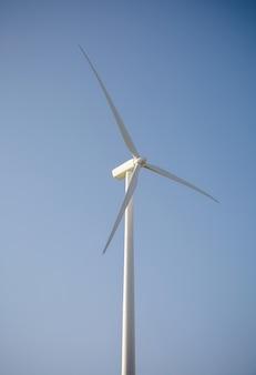 Close-up van windmolenturbine en bladen die elektriciteit opwekken over een blauwe hemelachtergrond. schoon en ecologisch energieproductieconcept.