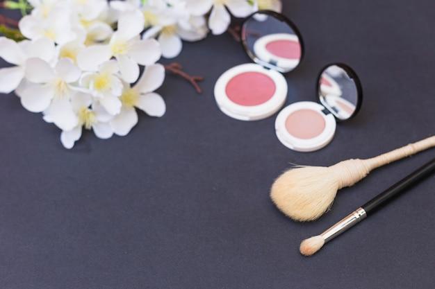 Close-up van witte bloemen; rouge en make-upborstel op grijze achtergrond