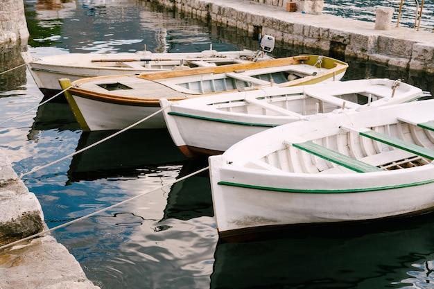 Close-up van witte boten die bij de pijler worden afgemeerd.