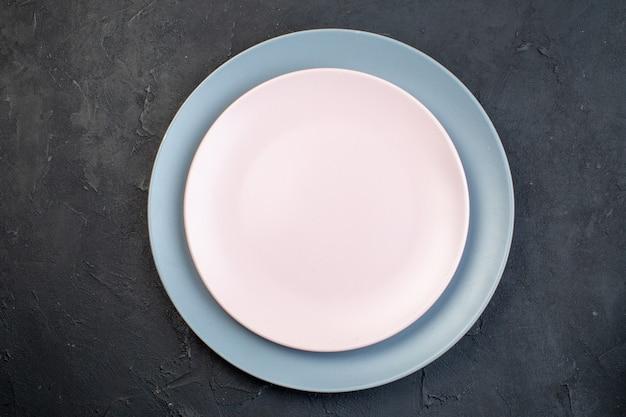 Close-up van witte en blauwe keramische lege platen op zwarte achtergrond met vrije ruimte