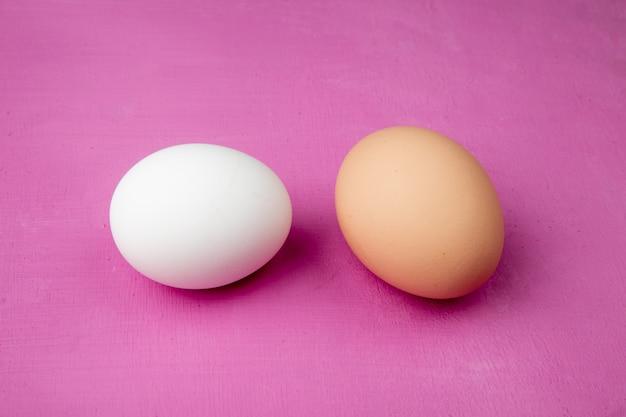 Close-up van witte en bruine eieren op paarse achtergrond met kopie ruimte