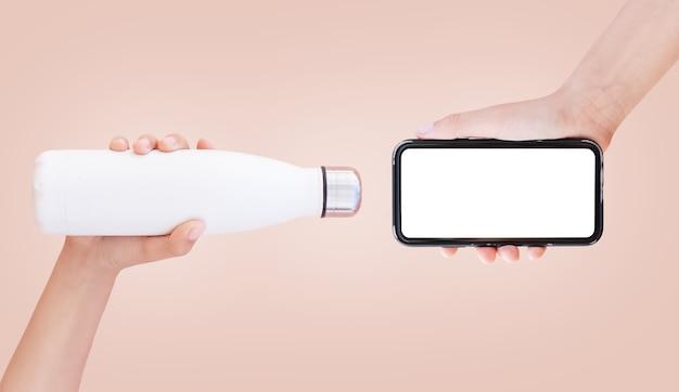 Close-up van witte fles en smartphone met mockup in handen, op lichtbruin.